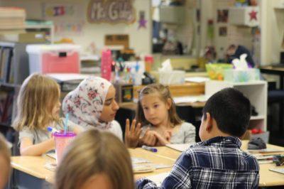 A student teacher helps children in a local classroom